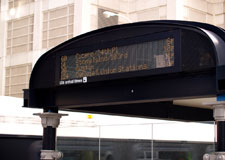 Photo of a digital bus arrival time display at a CTA bus shelter displaying arrival times for the next four buses.